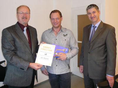 DA-Vorsitzender Walter Werner (l.) und Finanzvorstand Johannes Harzheim (r.) übergeben Unternehmer Christian Laabs die Ehrenurkunde des Verbands.